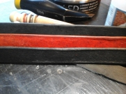 """The back side of the leather strips. Observe how the leather edge overflowed or """"burred"""" on the front black strap. This comes from not beveling enough or pushing too hard when burnishing."""